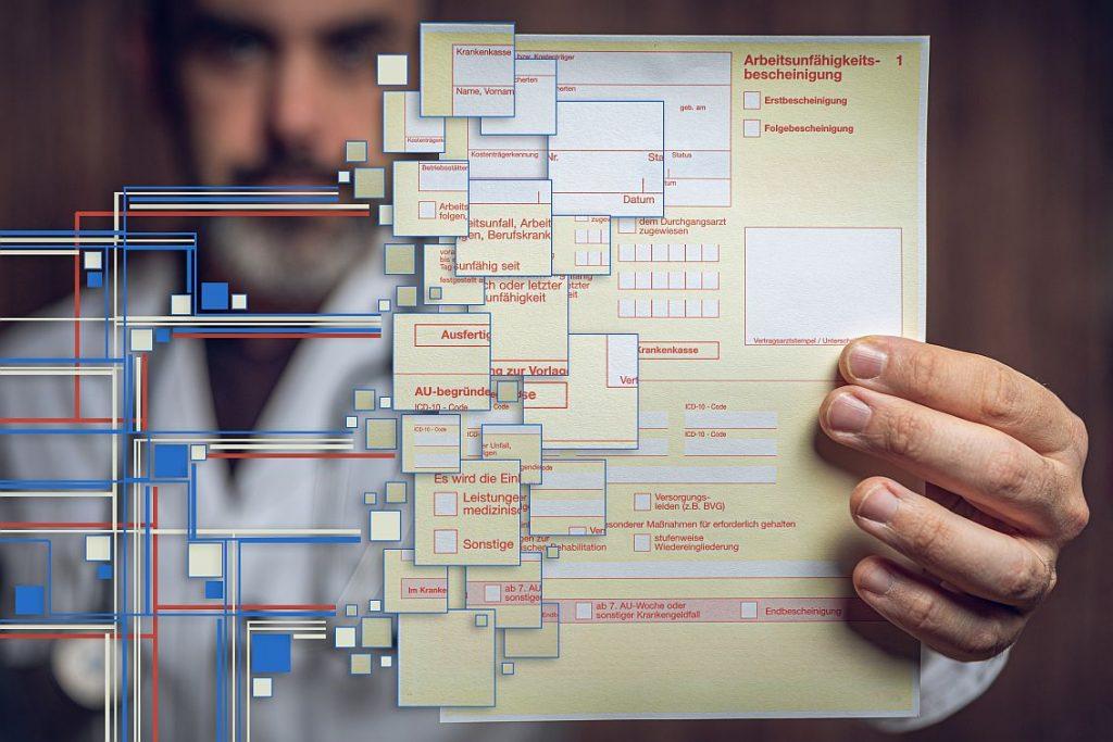 Man hält gelbe Arbeitsunfähigkeitsbescheinigung. Langsam wird sie digital - die Arbeitsunfähigkeitsbescheinigung. (Foto: © mpix-foto – stock.adobe.com)