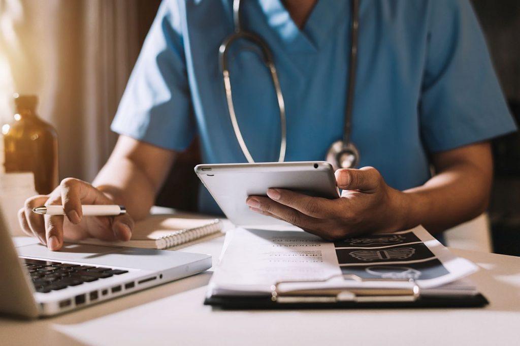 Man sieht den Oberkörper eines Arztes, der Laptop und Tablett nutzt, um Patientenbefunde zu bearbeiten. eKonsil ermöglicht es jetzt, sich bei der Behandlung von Penis- und Nierenzellkarzinomen zusätzliches Expertenwissen einzuholen. (Foto © mrmohock – stock.adobe.com)